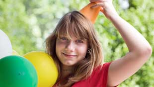 Girl with balloons and party hat
